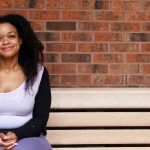 Melinda sits on a bench on campus.