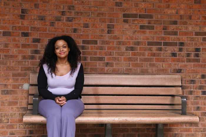 Melinda smiles, sits on a bench on campus.