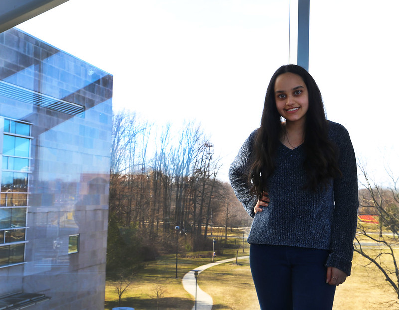 Roshni stands next to a glass window inside an academic building on campus.