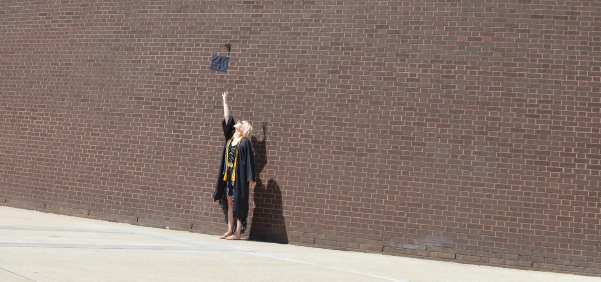 Amanda wears a cap and gown in front of a brick building.