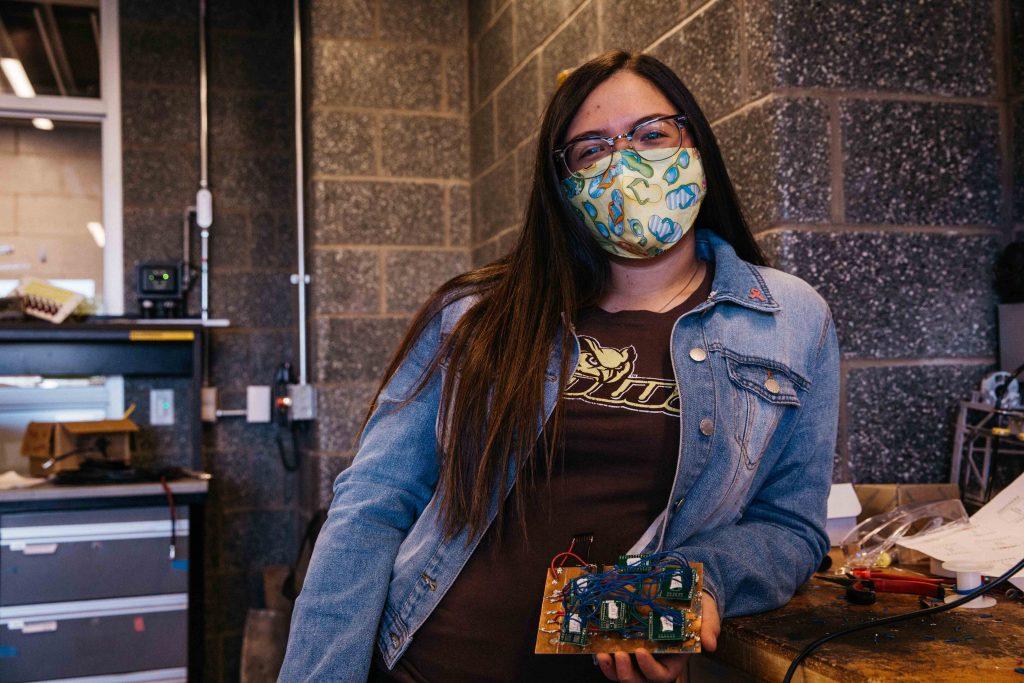 Giavana posing with her circuit board wearing a mask a rowan shirt.