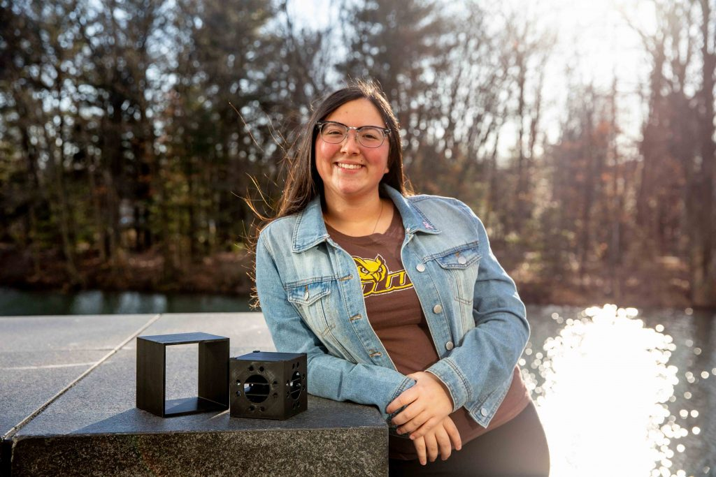 Giavana leaning against a stone with her cubesat satellite prototype next to her.