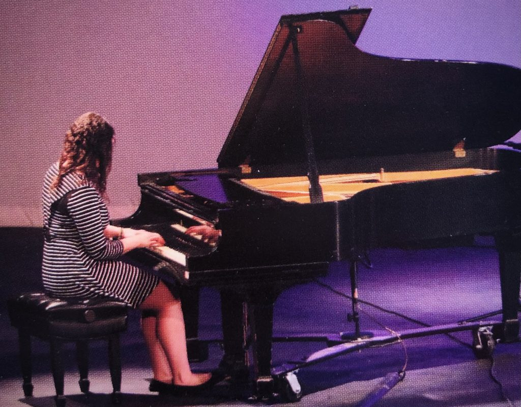 Mackenzie playing a piano on a stage.