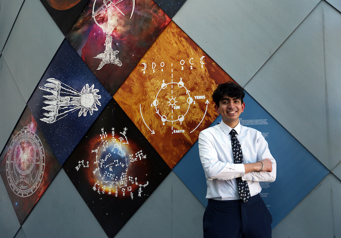 Gurkirat posing with his arms crossed while wearing a dress shirt and tie outside the observatory in the stem building.