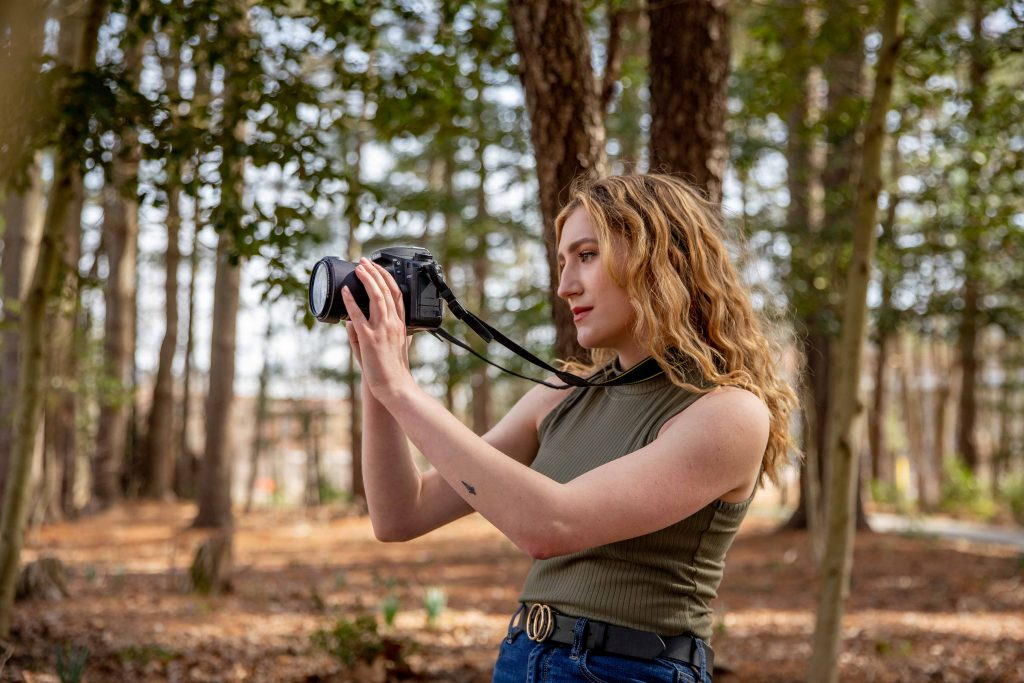 Jill takes a photo in the woods.