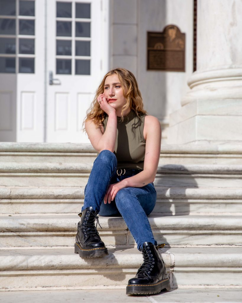 Jill looks off into the distance while sitting on Bunce Hall's steps.