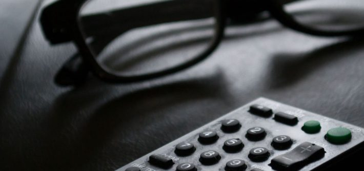 Stock image of eyeglasses and a remote control.