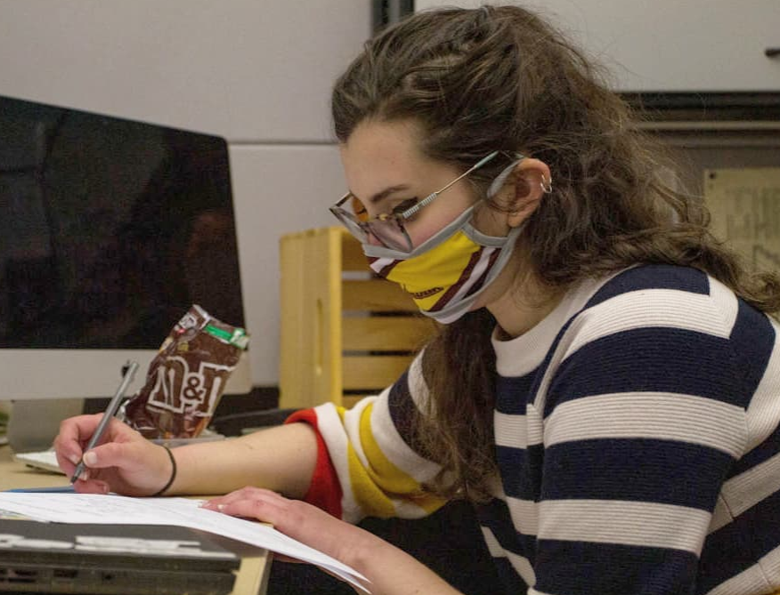 Tara writing on a sheet of paper with a mask.