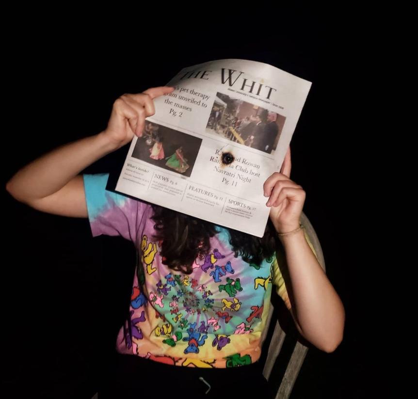 Tara in a dark room looking through a burnt hole in The Whitt newspaper.