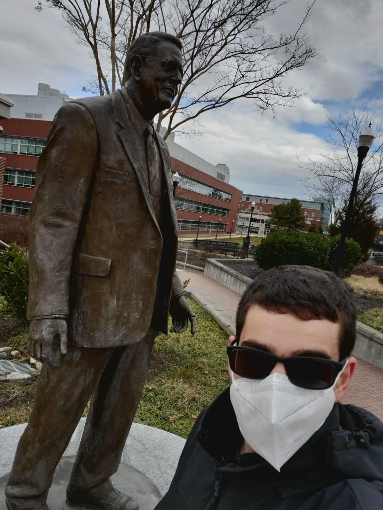 Ethan taking a selfie with the Henry Rowan statue in front of Savitz wearing a mask.