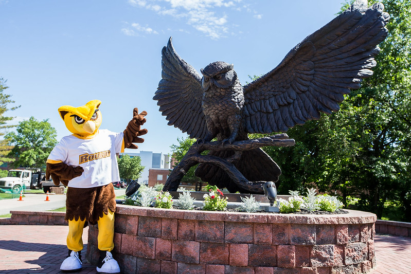 The Whoo RU mascot in front of the prof statue.