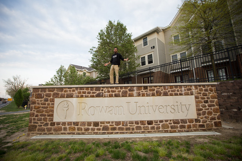 Student standing on top of the Rowan stone sign.