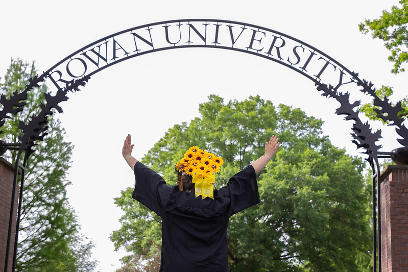 Student turned around showing cap off under the Rowan Arch.