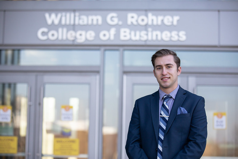 Brandon stands in front of the entrance to Business Hall.