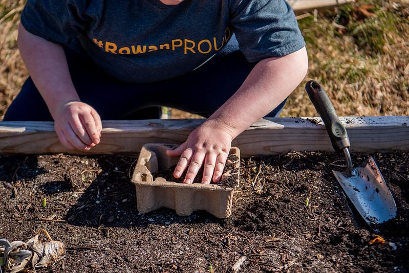 A child wears a Rowan shirt while gardening.