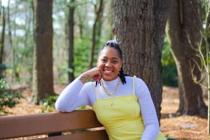 Ayanna smiles while sitting and leaning on a bench on campus.