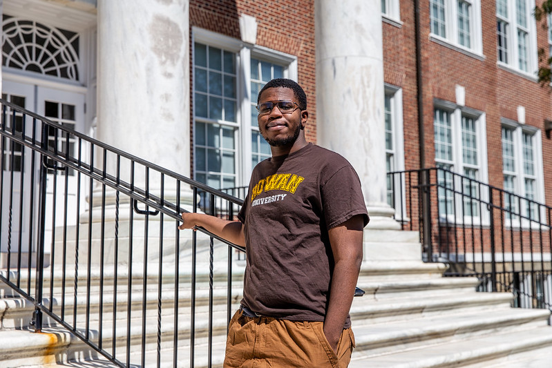 Alex stands on the steps of Bunce Hall.