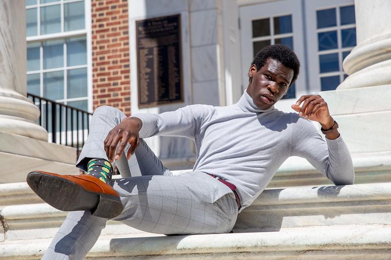 Joshua sits on the steps of Bunce Hall.