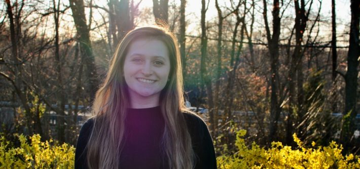 Vivian smiles, stands outside in a wooded area.