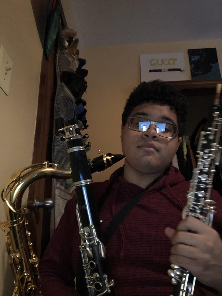 Selfie of Isaiah with a saxophone and two clarinets.