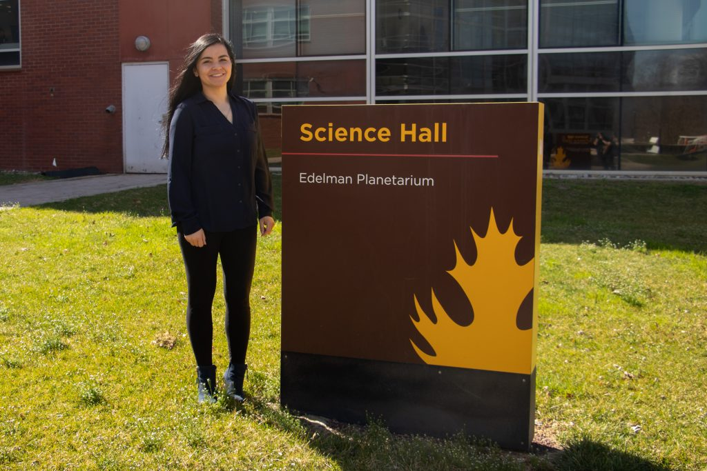 Holly poses next to the sign for Science Hall.