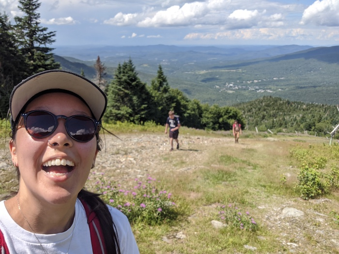 A picture of Hannah taking a selfie while on a hike.