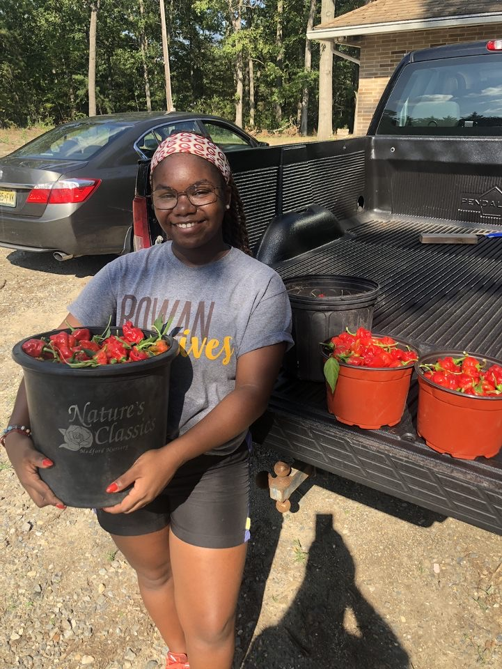 Dyone holds a bucket of peppers fresh from the farm.