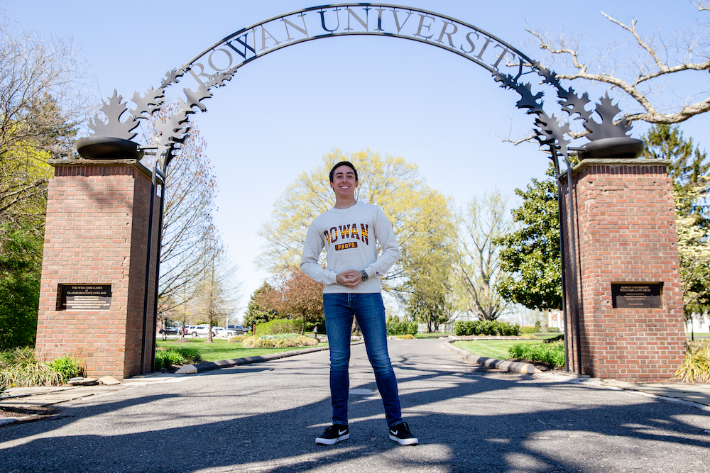 JT stands in front of the Rowan University archway near Bunce Hall.