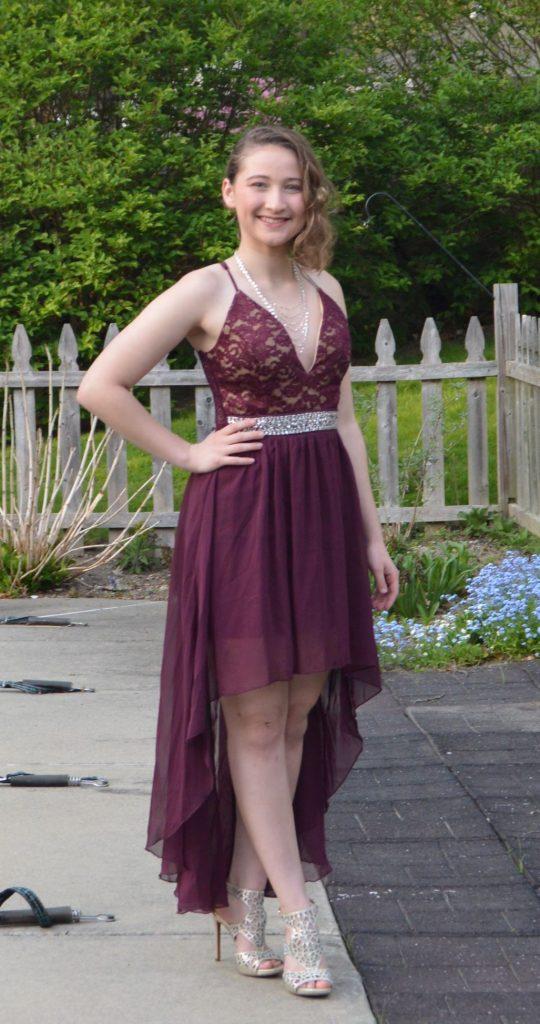 Kayla in a fancy purple dress with heels outside in a backyard.