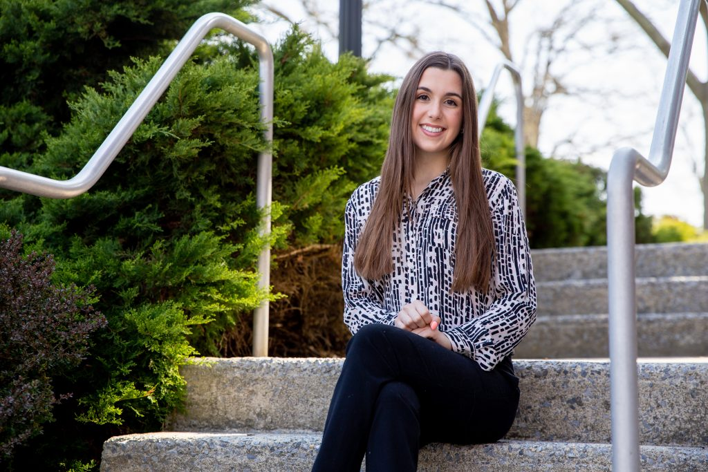 Loredonna sits on steps outside on campus.