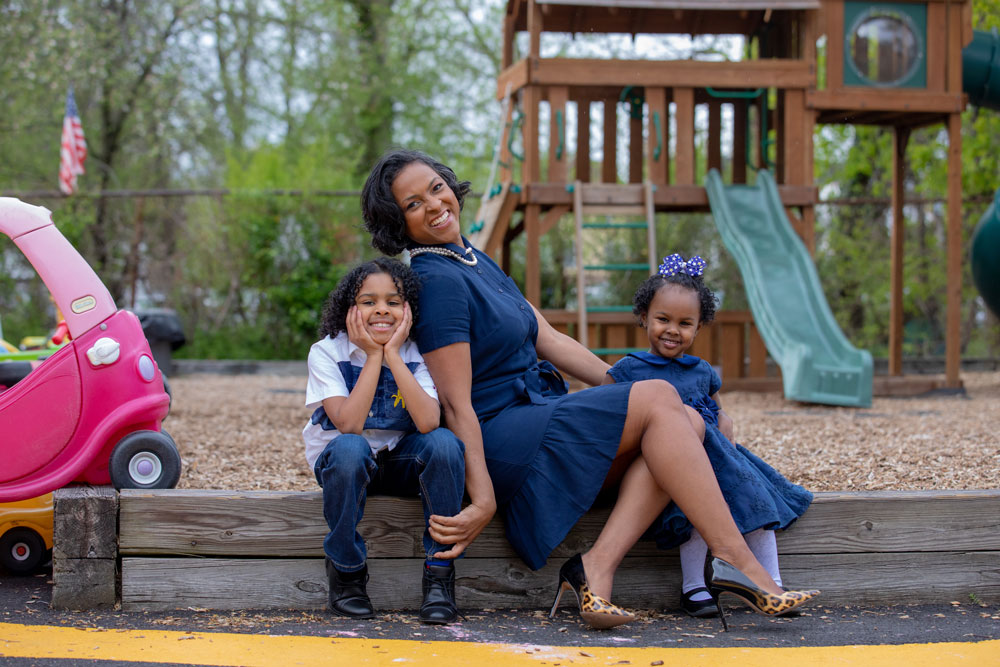 Marguerite sits with her children at a playground.