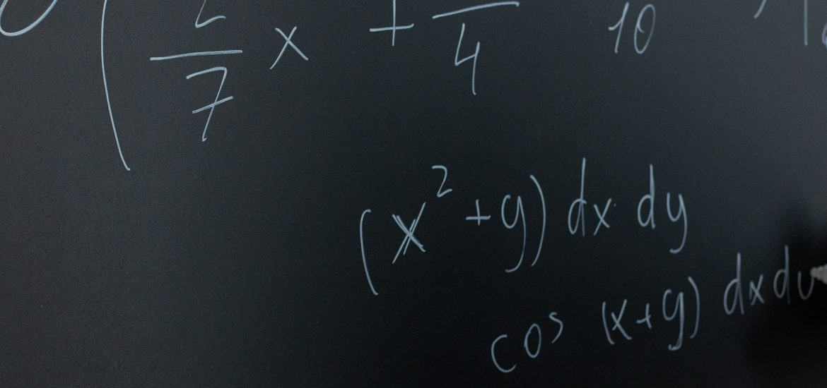 Stock image of math equations being written on a blackboard with chalk in hand.