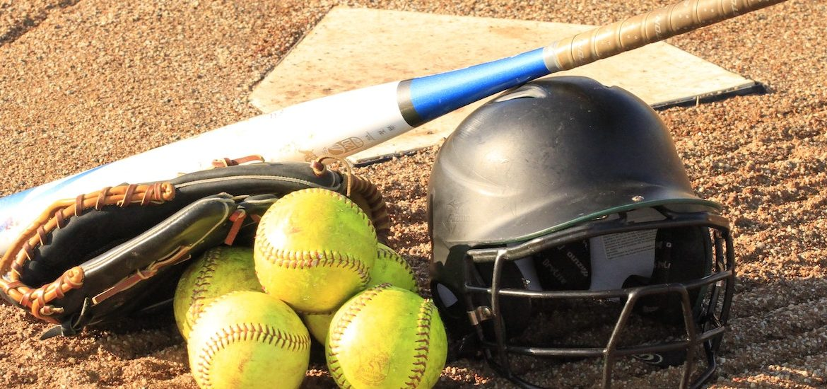 Stock image of a softball home plate with a helmet, three softballs and a bat.