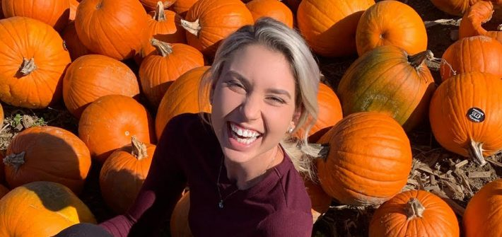 Outdoor photo of Sara smiling in a pumpkin patch.