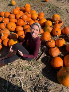 Sara laughing and sitting in a pumpkin patch.