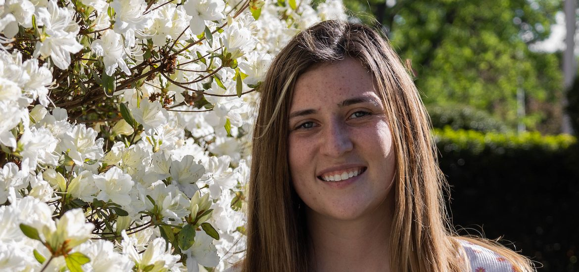 Hannah smiles while standing next to a white flowering plant on campus.