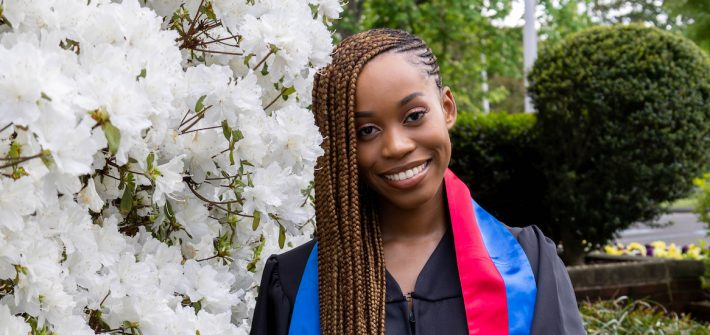 Esther wears her graduation gown and stands in front of campus greenery.