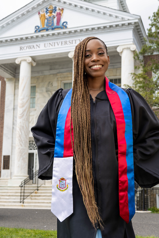 Esther smiles wearing her graduation gown with Bunce Hall in the background.
