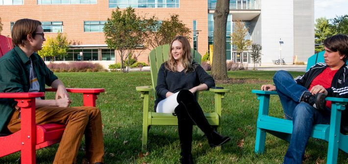 Alexandra sits and talks with friends on campus.