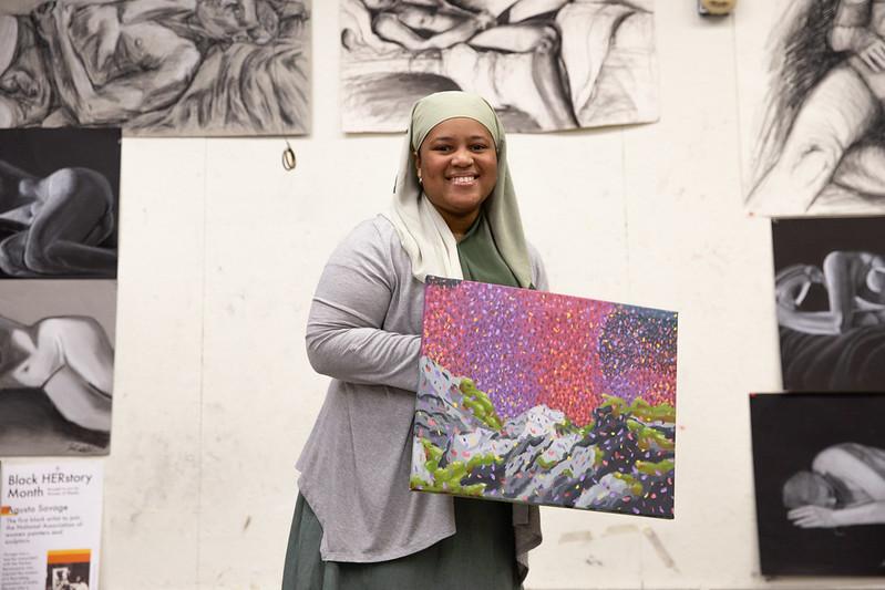 Sumayyah posing with a piece of artwork.