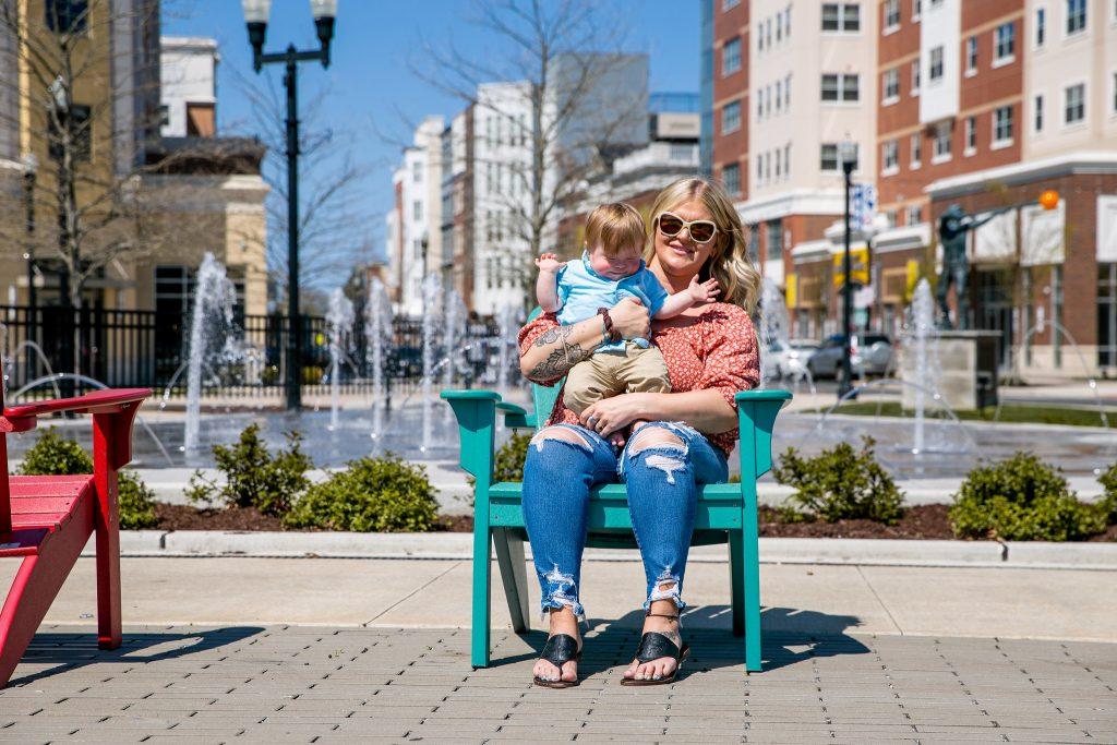 Victoria sits and hugs her son on Rowan Boulevard.