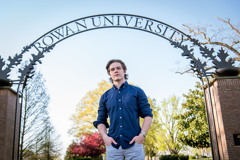 Liam stands in front of the Rowan arch.