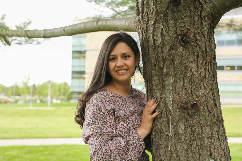 Khrissy standing next to a tree outside on campus.
