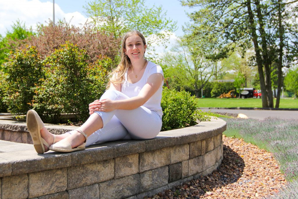Cam sits on a paver bench on campus.