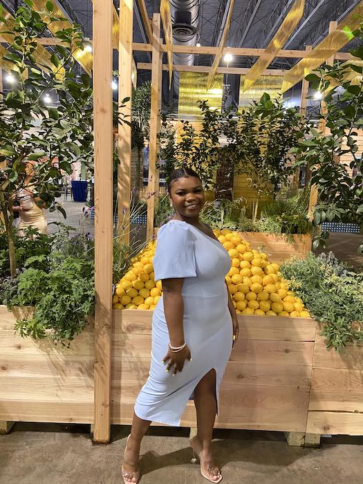 Dyone poses by a pile of lemons and hanging plants at the Philadelphia Garden Convention, wearing a lovely baby blue dress.