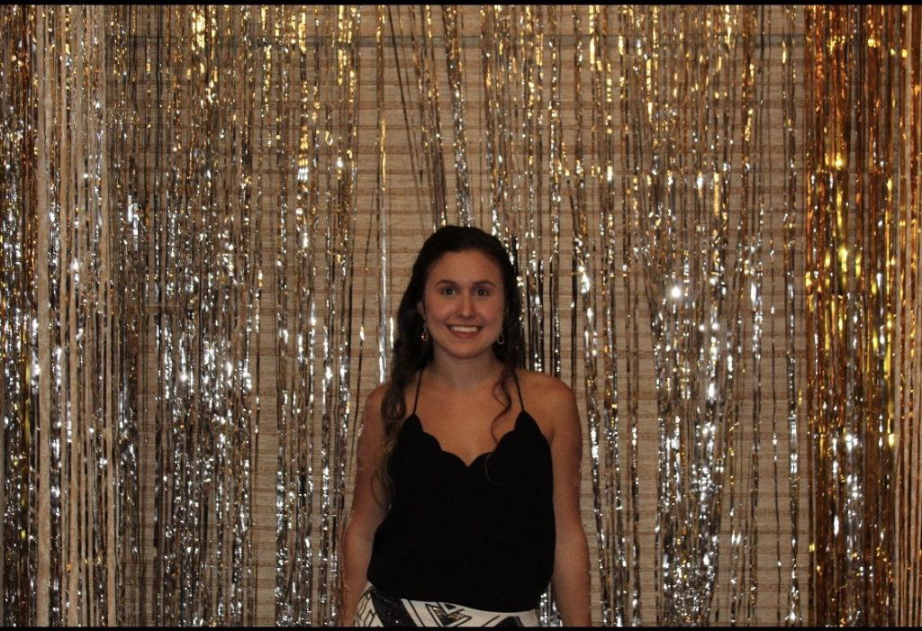 Mallory poses in front of a glittery backdrop.