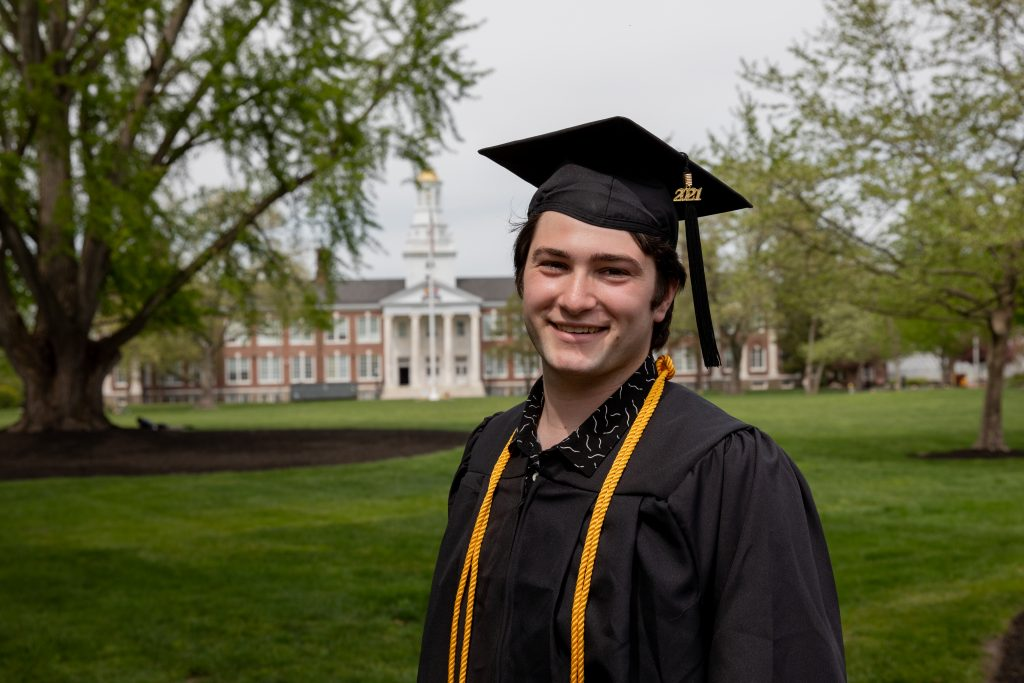 Josh standing in his cap and gown with Bunce Hall in the background.