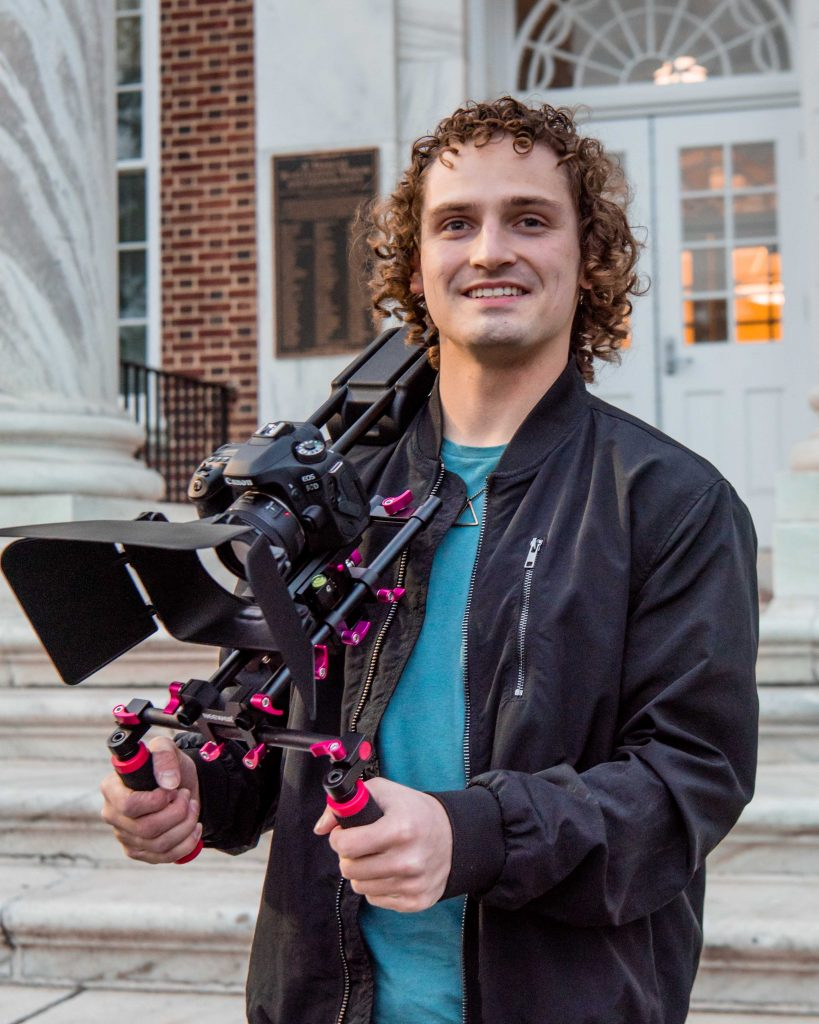Adam holding his video gear and looking at the camera at Bunce.