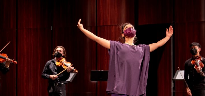 Amanda dancing on stage in a purple outfit and mask with the ensemble around her.
