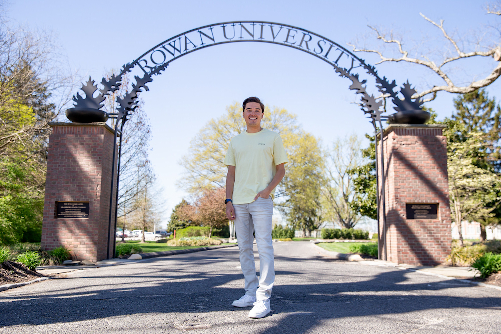 Anthony stands confidently in front of the Rowan arch.